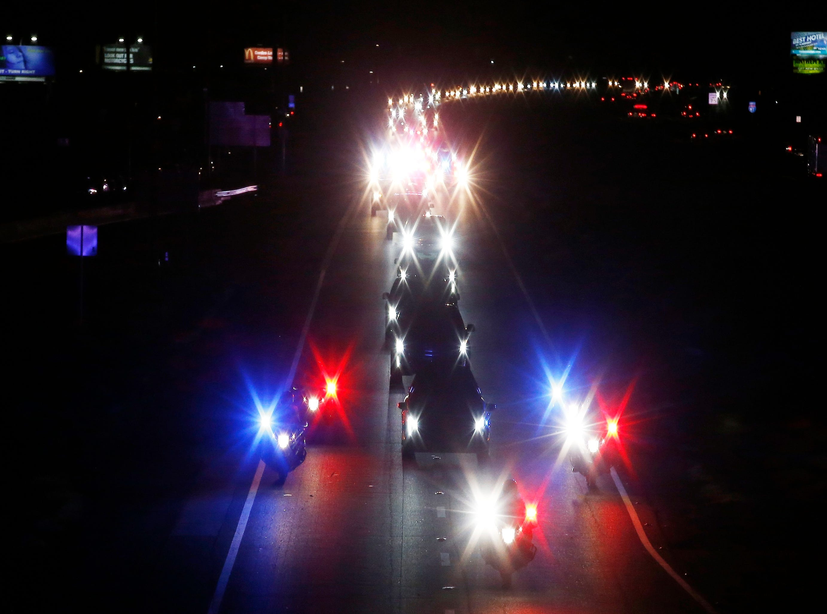 With a police escort, a long procession accompanies the hearse carrying the late Arizona Sen. John McCain along Interstate 17 on the way to Phoenix on Aug. 25, 2018, in Anthem.