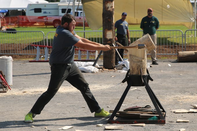 Brian Shuknecht, 22, finishes his final swing to cut a block of wood in half. The lumberjack competition was new to the fair this year.