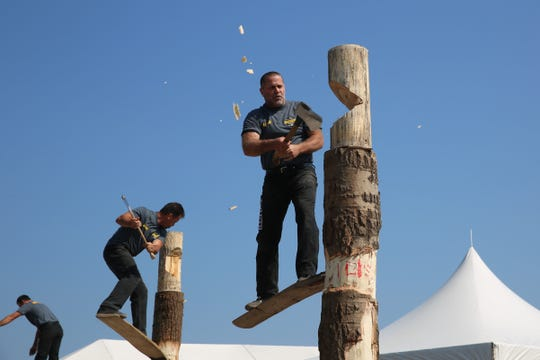 Richard Jordan (right), a competitor in the lumberjack springboard competition on Sunday, finishes a cut toward the top of the tree. The object of this game was to climb up the tree trunk and chop off the top.