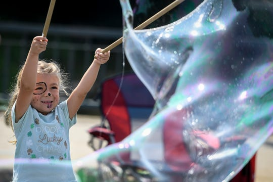 Tuleya McGovern, 5, of York City, creates bubbles along Market Street during the final day of the Yorkfest Fine Arts Festival along the York County Heritage Rail Trail, Sunday, August 26, 2018. John A. Pavoncello photo