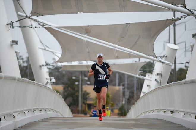 A runner crosses over South Monroe Street via the pedestrian bridge during the Tallahassee Marathon, Sunday Feb. 4, 2018. The bridge connects to Cascades Park.
