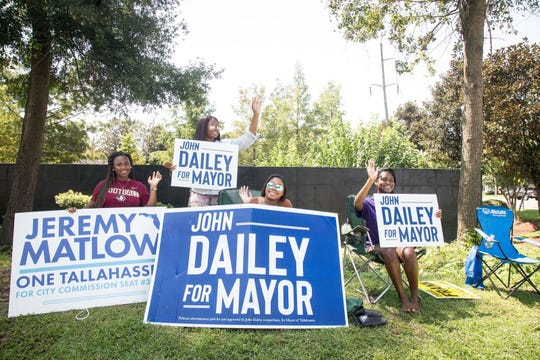 Supporters tout their candidates on the final day of early voting near BL Perry Branch of the Library.