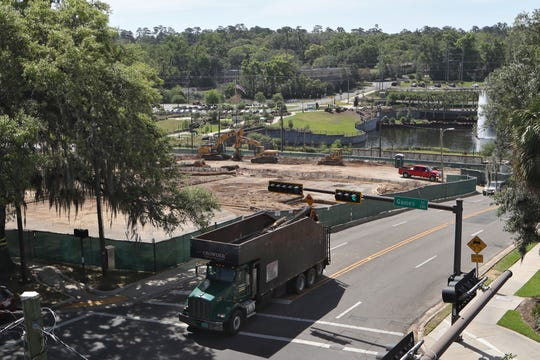 A truck drives off with a load of lumber on Thursday, April 5, 2018 from the site at Cascades Park that is being excavated for a new $158 million housing and retail complex.