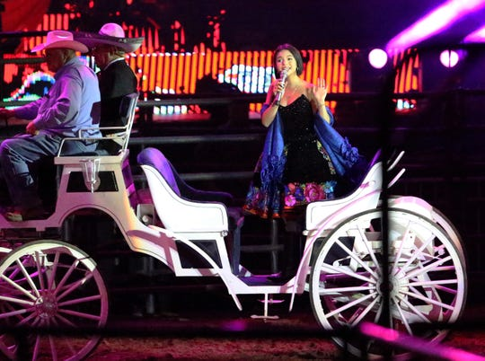 Angela Aguilar, 14, enters the arena in a white carriage Saturday night.