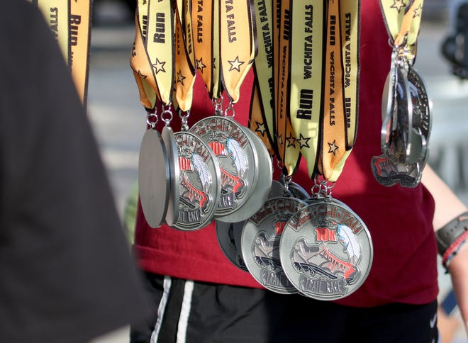 Volunteers hold medals for half-marathon and 10K runners on the final day of the Hotter'N Hell Hundred Sunday, Aug. 26, 2018, at the J.S. Bridwell Agricultural Center.