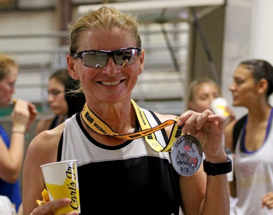Rosa Buth holds her 10K medal on the final day of the Hotter'N Hell Hundred Sunday, Aug. 26, 2018, at the J.S. Bridwell Agricultural Center.