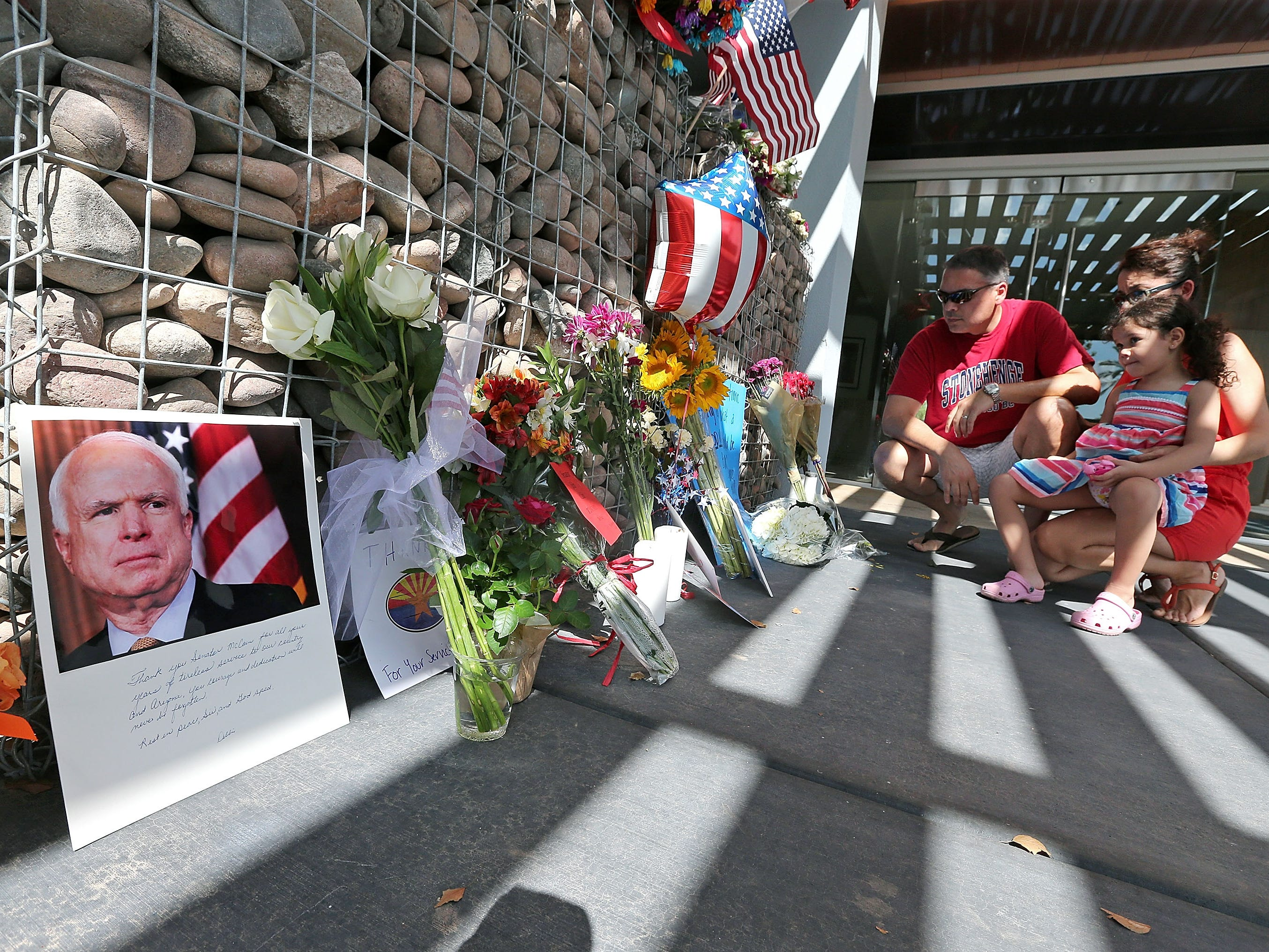 A family kneels down and place flowers at a small memorial to pay their respects to the late Sen. John McCain outside his office on Aug. 26, 2018 in Phoenix, Ariz.