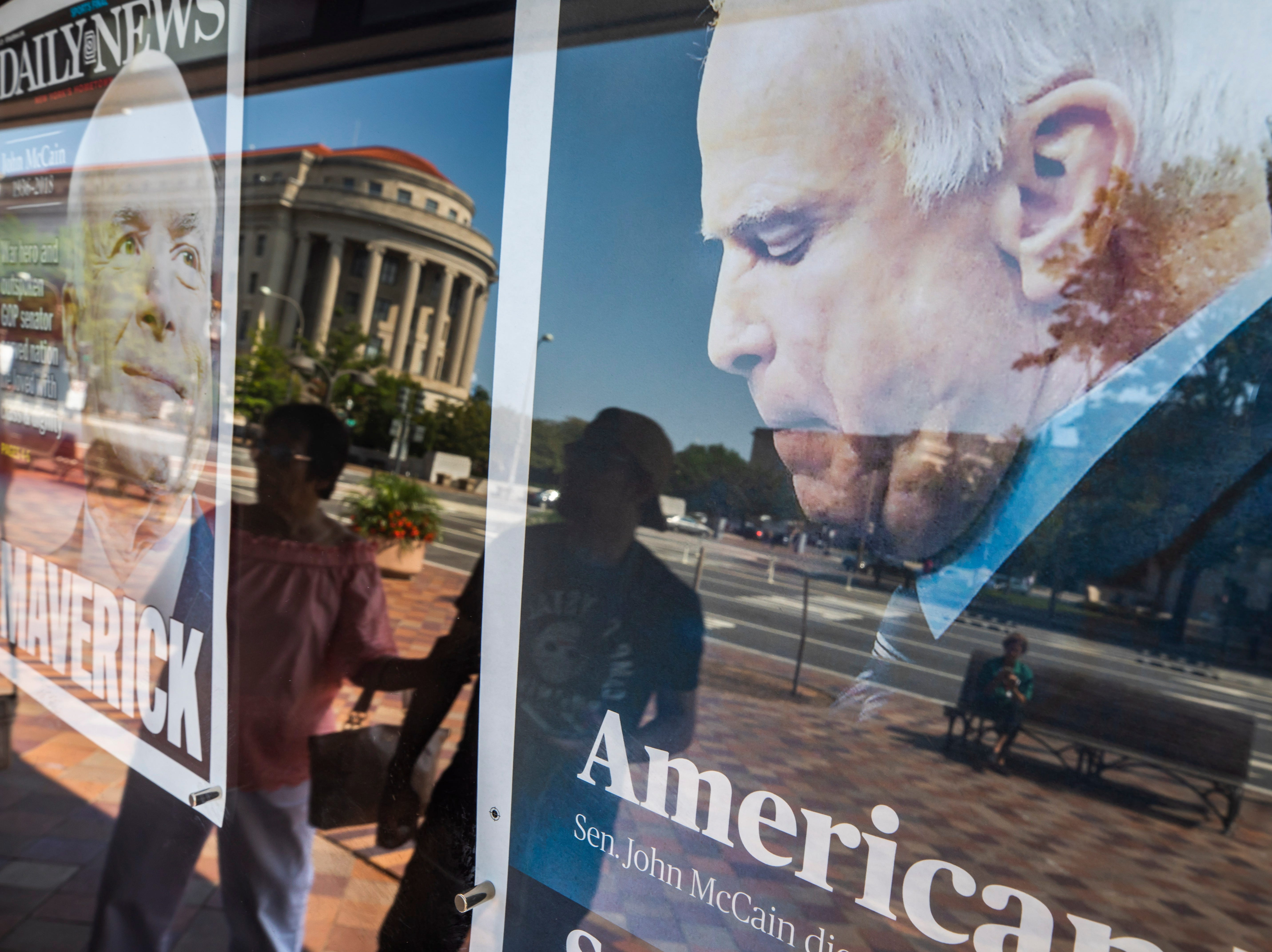 Pedestrians are reflected in the front page of the Fayetteville Observer, right, and the NY Daily News, which memorialize Republican Senator John McCain outside the Newseum in Washington, DC, on  Aug. 26, 2018.