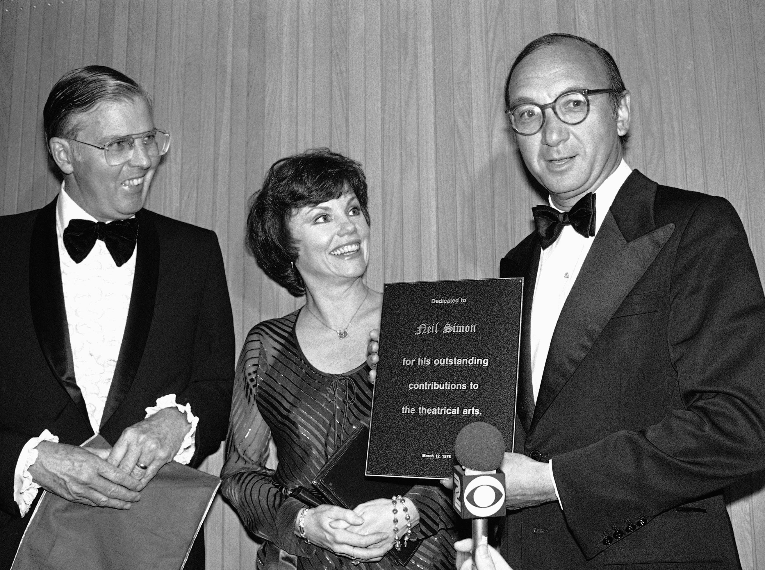 Playwright Neil Simon receives an honorary plaque during ceremonies of the grand opening of the Long Beach Convention and Performing Arts Center, Sunday, March 12, 1978 in Long Beach, Calif. with Simon in his wife, actress Marsha Mason and Long Beach Mayor Tom Clark. Simon was cited for his contributions to theatre, TV and motion pictures. (AP Photo/George Brich)