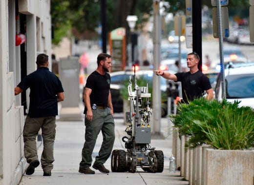 Bomb squad police prepare a robot to enter a parking garage a block away from the scene of a multiple shooting at the Jacksonville Landing Sunday, Aug. 26, 2018, during a video game competition in Jacksonville, Fla. A gunman opened fire Sunday during an online video game tournament that was being livestreamed from a Florida mall, killing multiple people and sending many others to hospitals, authorities said.   (Will Dickey/The Florida Times-Union via AP) ORG XMIT: FLJAJ111