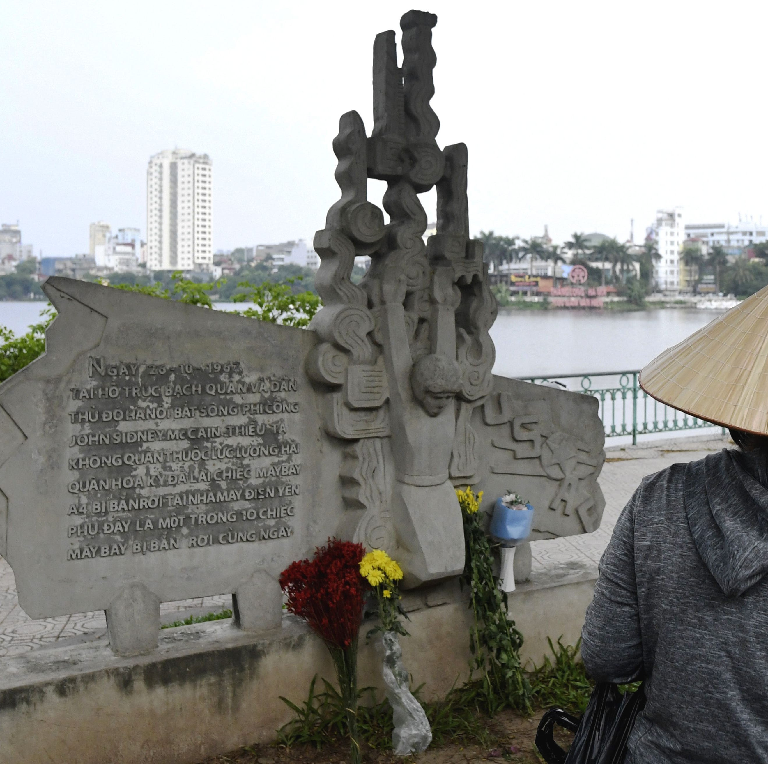 Flowers for the late Sen. John McCain on Aug. 25, 2018, at a sculpture depicting his capture in 1967 in Hanoi.