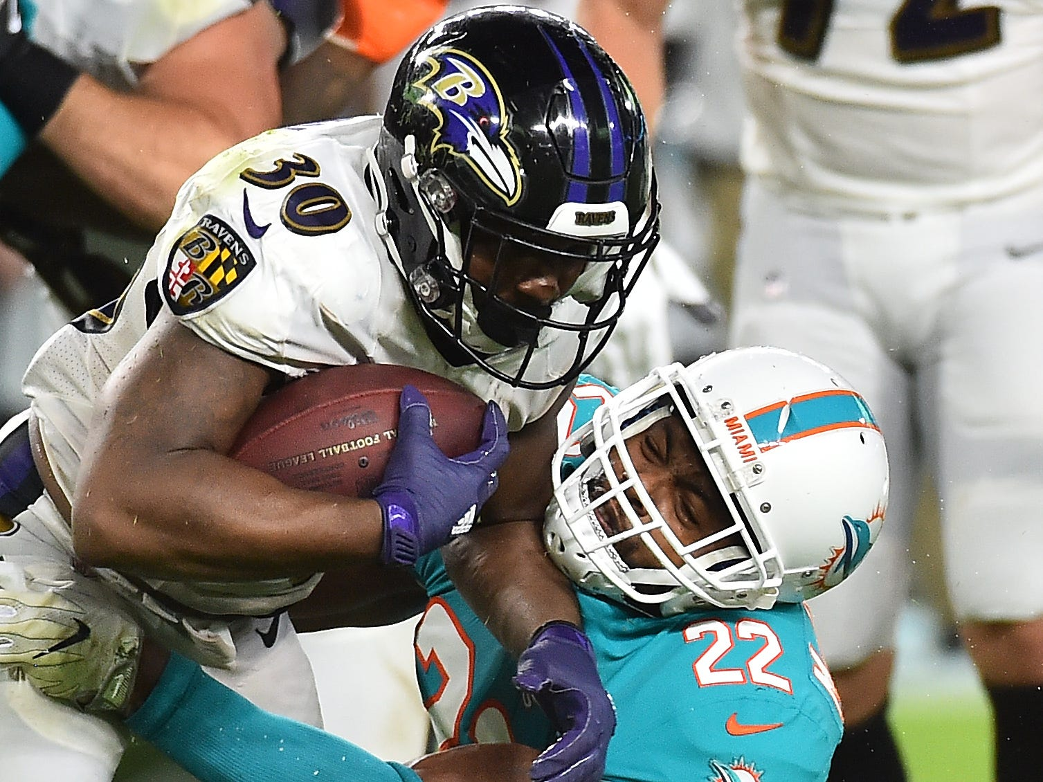 Dolphins defensive back T.J. McDonald wraps up Ravens running back Kenneth Dixon during the first half.