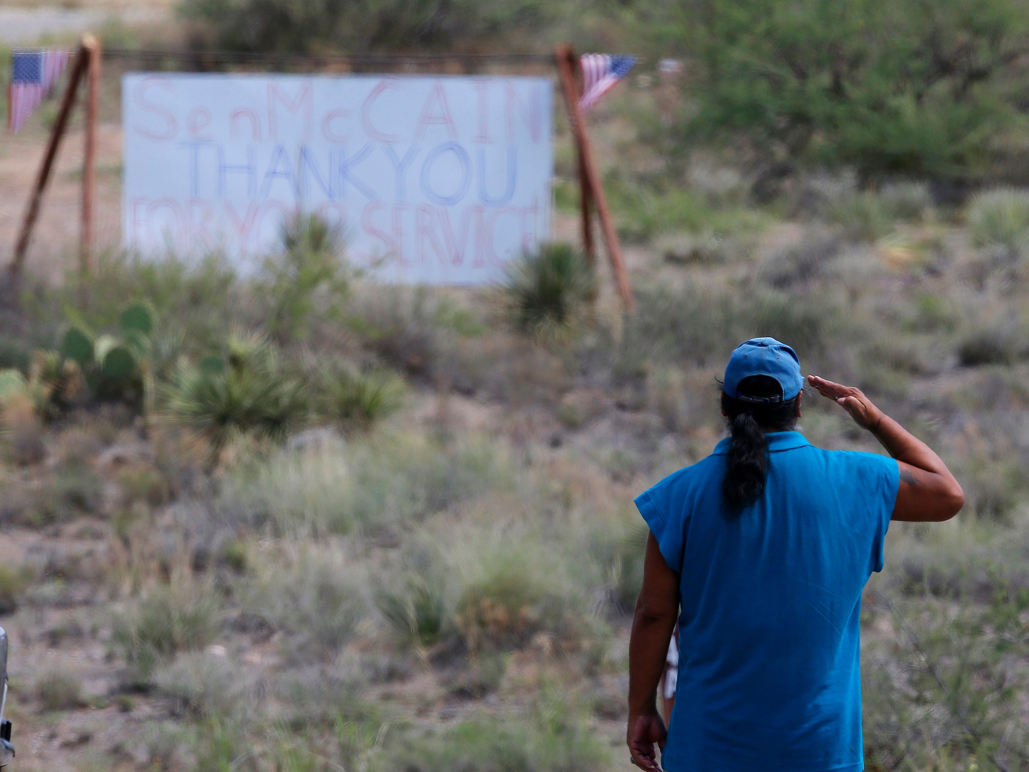 A military veteran pays his respects, as John McCain has discontinued medical treatment for an aggressive form of brain cancer, at the entrance to the McCain ranch complex in Cornville, Ariz., Saturday, Aug. 25, 2018.