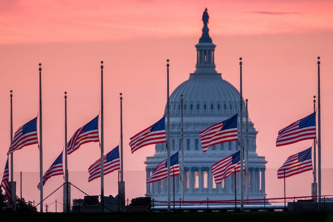 Flags flying a half-staff in honor of Sen. John McCain, frame the U.S. Capital at daybreak in Washington, Sunday, Aug. 26, 2018.