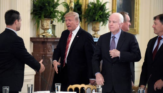 President Donald Trump reached out to shake hands with Sen. Todd Young, R-Ind., as he arrived for a meeting with Republican senators on health care in the East Room of the White House on June 27, 2017. Sen. John McCain, R-Ariz., who later cast the deciding vote against the president, watches.