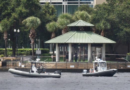 Law enforcement boats patrol the St. Johns River at the scene of a multiple shooting at the Jacksonville Landing Sunday, Aug. 26, 2018 in Jacksonville, Fla. A gunman opened fire Sunday during an online video game tournament that was being livestreamed from a Florida mall, killing multiple people and sending many others to hospitals, authorities said.   (Will Dickey/The Florida Times-Union via AP) ORG XMIT: FLJAJ113