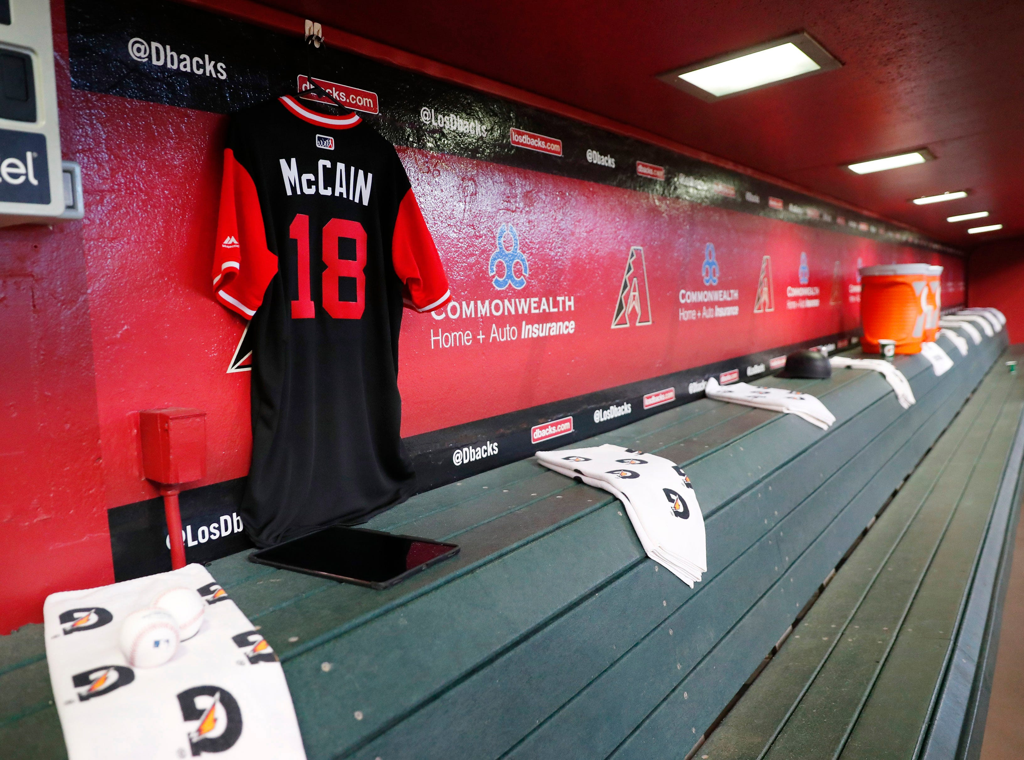 A jersey for Sen. John McCain hangs in the dugout before the Arizona Diamondbacks play against the Seattle Mariners at Chase Field. The six-term Arizona senator died Saturday at age 81.