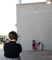 Mom Haley Tabor takes a photo of kindergartener Breland, standing, before going inside the new Wylie East Elementary School on Monday.