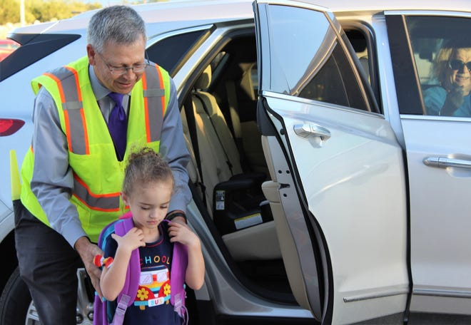 Wylie ISD Superintendent Joey Light helps first-grader Talia Hutchins adjust her backpack as she arrives Monday for the first day of classes at the new Wylie East Elementary School.