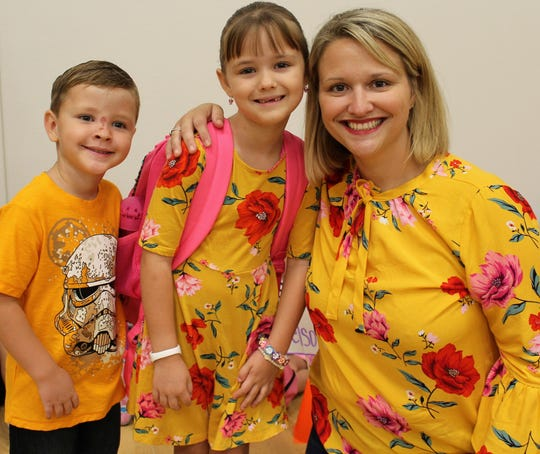 First-grader Madelaine McClendon, center, and her mother, Effie, wore matching clothes to the first day of school. Brother Mason, who is in pre-kindergarten, kept the color theme going but chose a different T-shirt design.