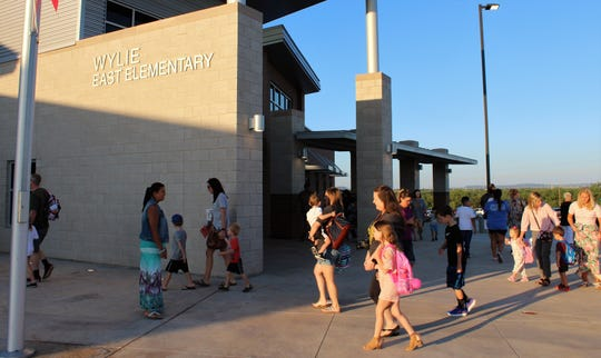 Students and their escorts arrive at the new Wylie East Elementary campus for the first day of school Monday.