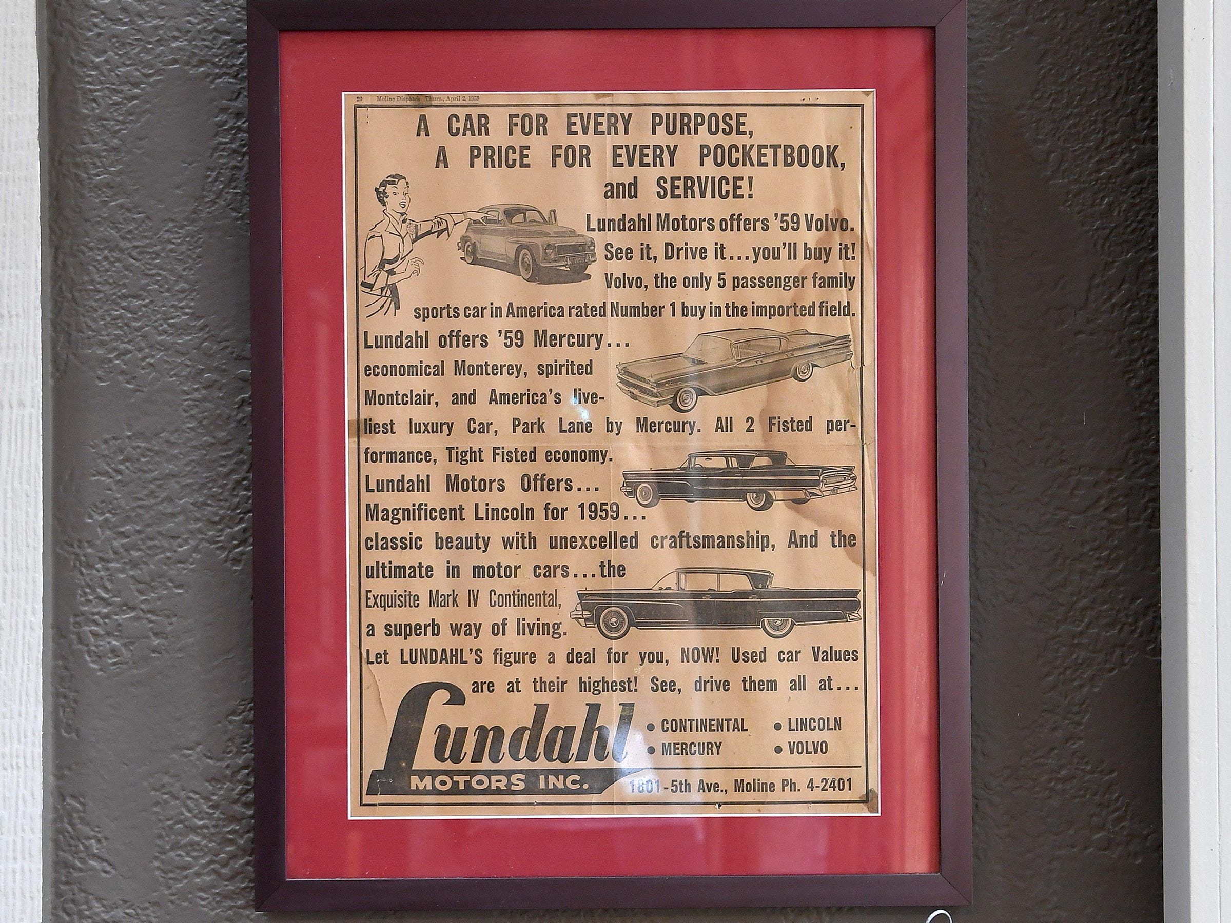 A poster showing the legacy of Annie Lundahl's father's car dealership hangs on the wall of the house she shares with her wife Mary Ann Myers in North Asheville.