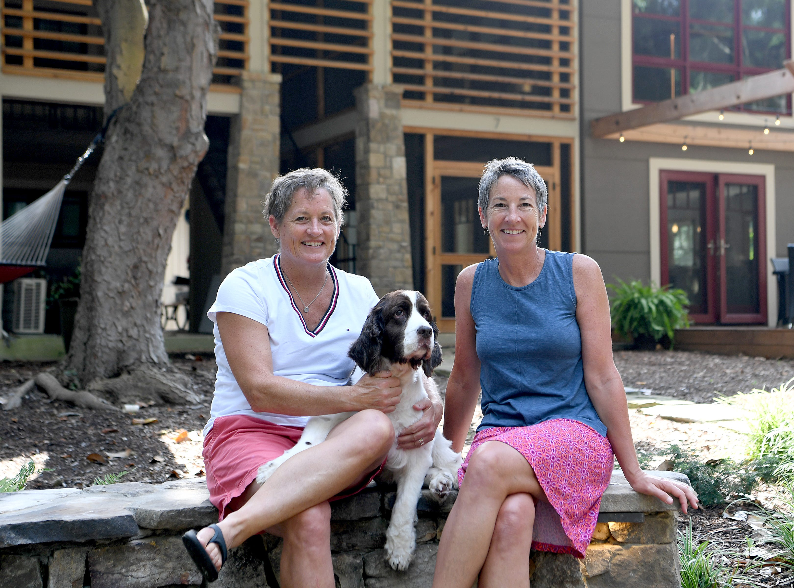 Mary Ann Myers, left, and Annie Lundahl pose with their English Springer Spaniel, Zach, outside their 1350 square-foot home that was once an apartment building in North Asheville. The couple renovated the building and moved in January of last year.