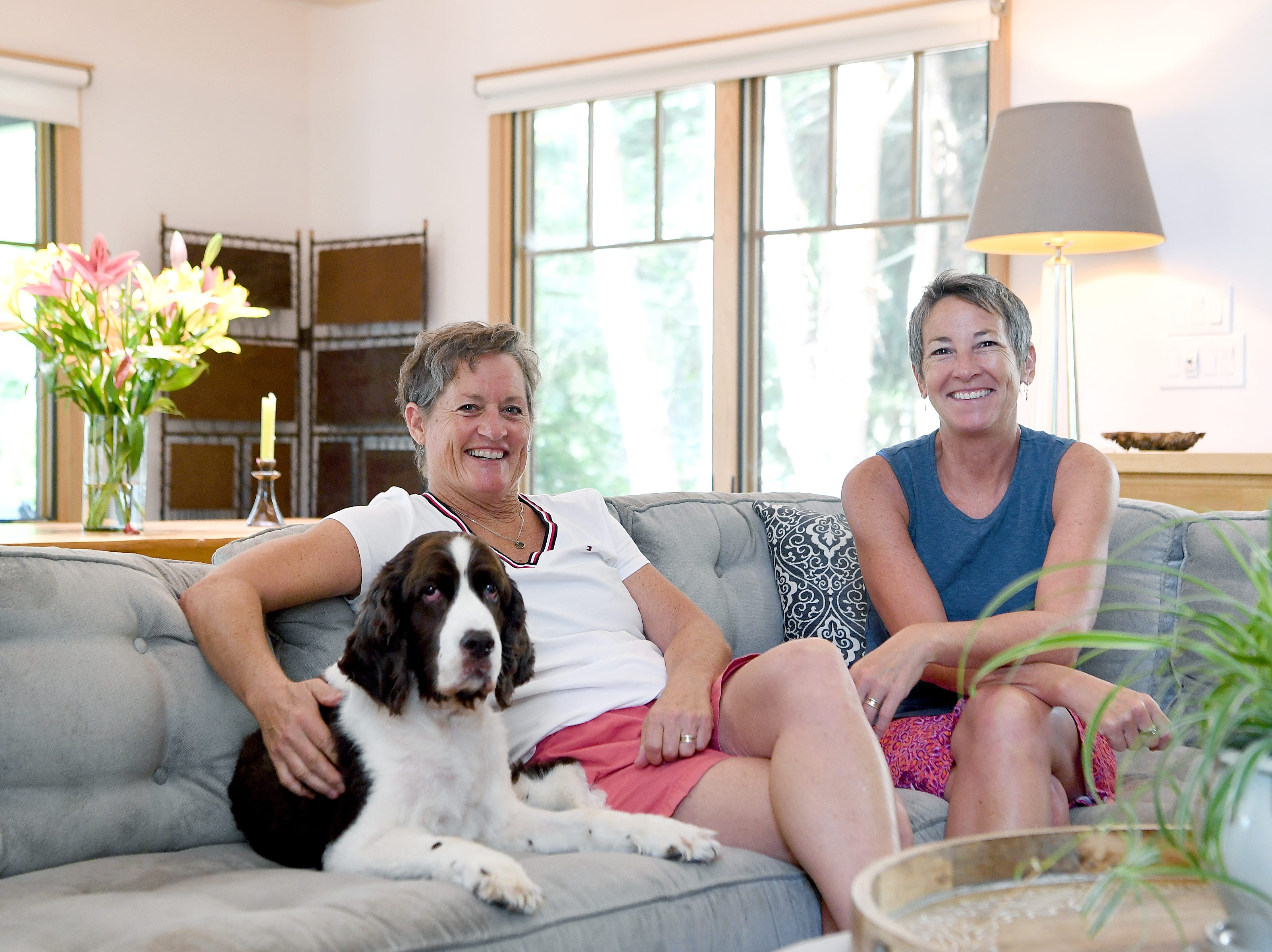 Mary Ann Myers, left, and Annie Lundahl pose with their English Springer Spaniel, Zach, inside their 1350 square-foot home that was once an apartment building in North Asheville. The couple renovated the building and moved in January of last year.
