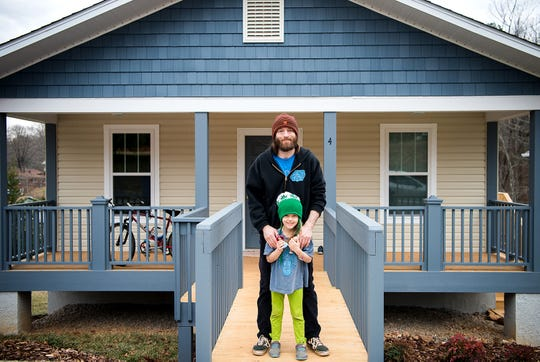 An Asheville Area Habitat homeowner stands in front of his Green Built certified home.