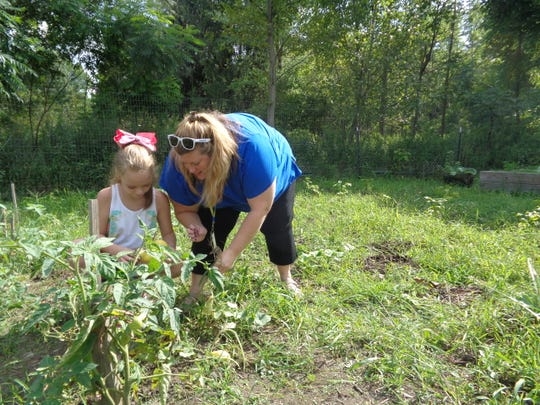 Molly Goosman, right, helps Nevaeh Kille, a fourth-grade student at Homer Brink Elementary School, pick peppers at the Spartan Garden. All vegetables are donated to needy families throughout the district or organizations such as CHOW or sold to buy food for the families.