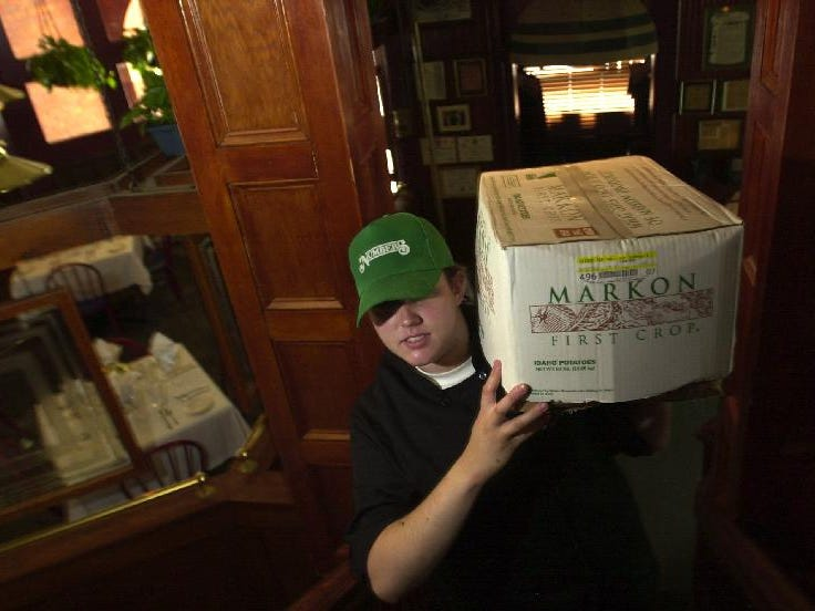 Chef Tiffany Sexton hefts a 50 pound box of potatoes up the stairs to Number 5 Restaurant's kitchen in July of 2003.