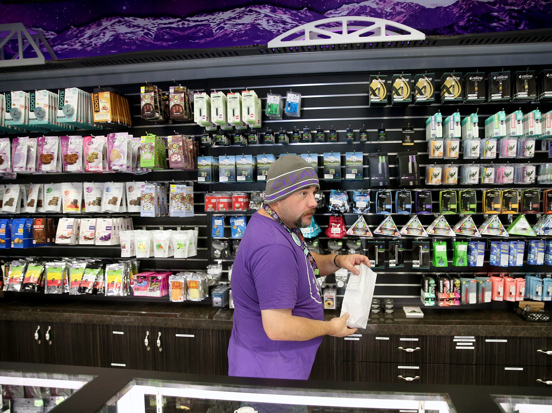 Luc Martin, a bud tender at Clear Choice Cannabis on Highway 303 in East Bremerton, fills a customer's order on Monday.