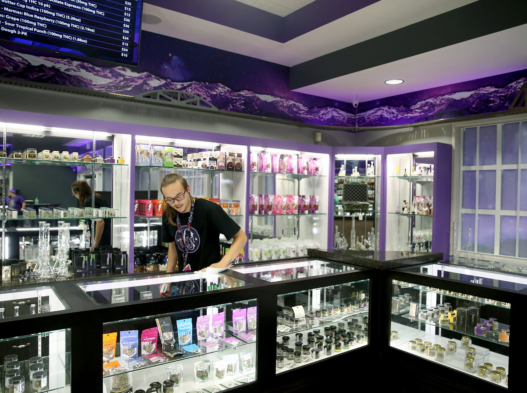 Clear Choice Cannabis bud tender Alex Wonser cleans display cases on Monday.