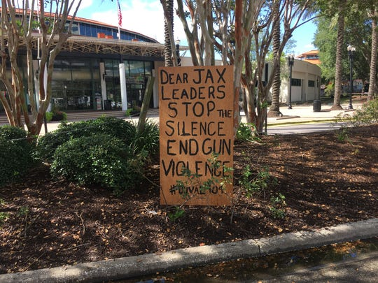 Handmade signs were placed outside the entrance of Jacksonville Landing, where two people were killed and several injured after a shooting during a Madden video game tournament before the suspected gunman killed himself.