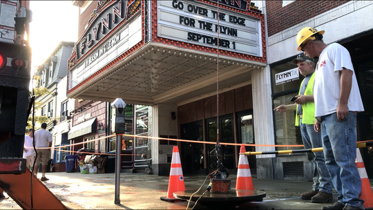 Burlington Public Works Department employees lift a manhole outside the Flynn Theatre after a fire-service water line burst Monday morning, Aug. 27, 2018.