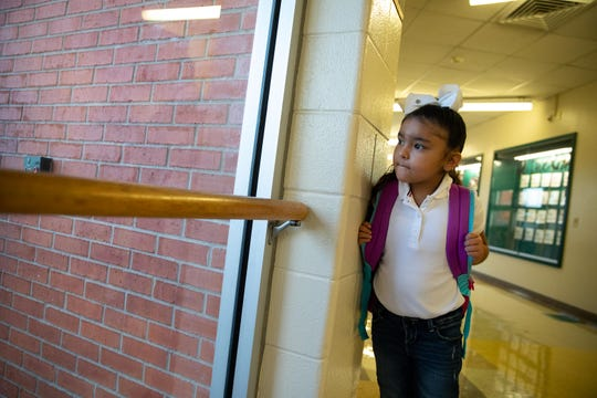 A young girl looks out the window in the entrance of Dawson Elementary on the first day of school on Monday, Aug. 27, 2018.
