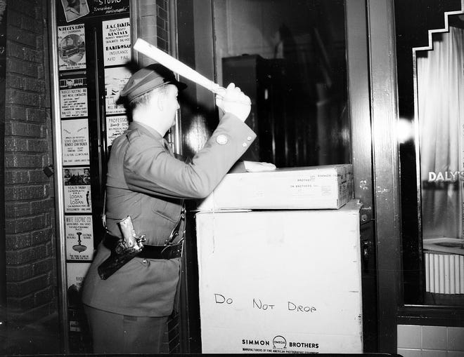 An air-raid warden made his rounds on Peoples Street, stopping to check for a light in the window of Daly's Camera Store during a blackout and curfew on Jan. 29, 1942.