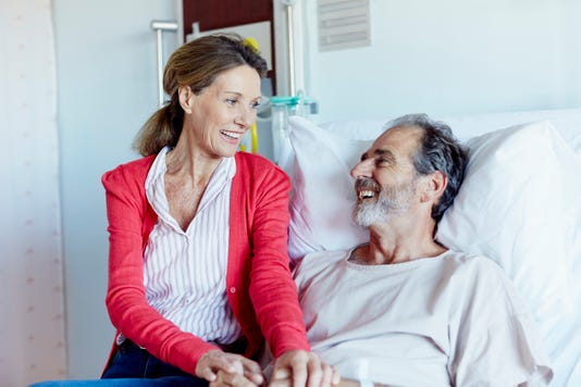 Woman Visiting Man In Hospital Ward