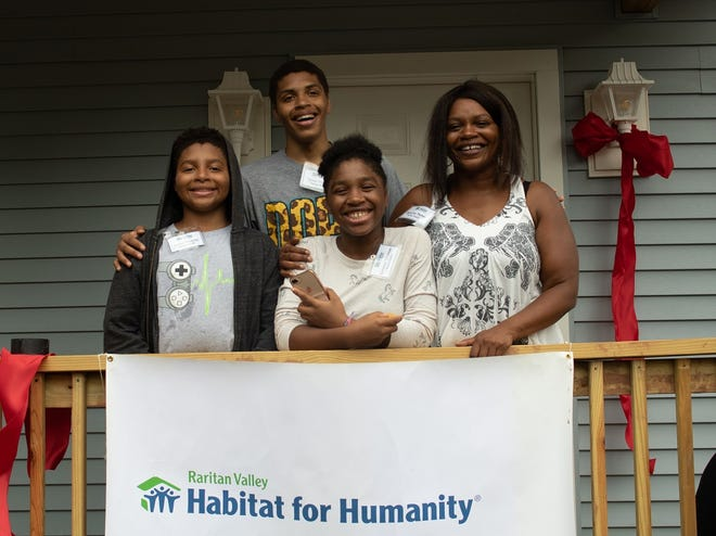 (Left to right) Tyelur, Tavier, Tameron and their mother, Tania-Sue Thomas stand in front of the home Tania-Sue built with the help of Raritan Valley Habitat for Humanity, her family and hundreds of community volunteers at her home dedication ceremony on Saturday, Aug. 11.