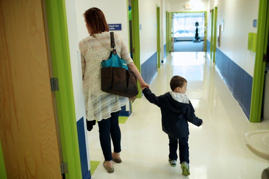 Erica Hammel and her son Wyatt Rewoldt hold hands as they leave a therapy session in April 2016.