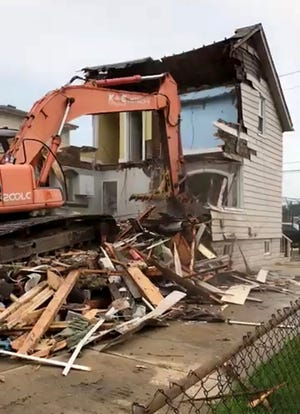 A wrecking crew tears down Erica Hammel's house in St. Clair Shores on Monday, Aug. 27, 2018.