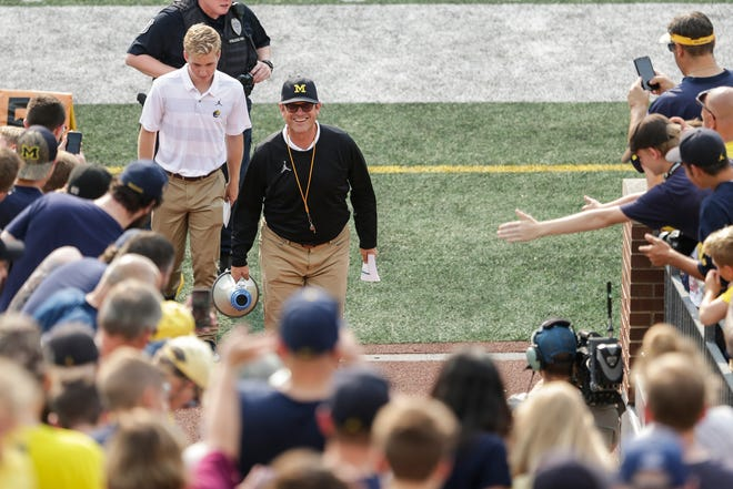 Michigan head coach Jim Harbaugh smiles at fans Sunday.