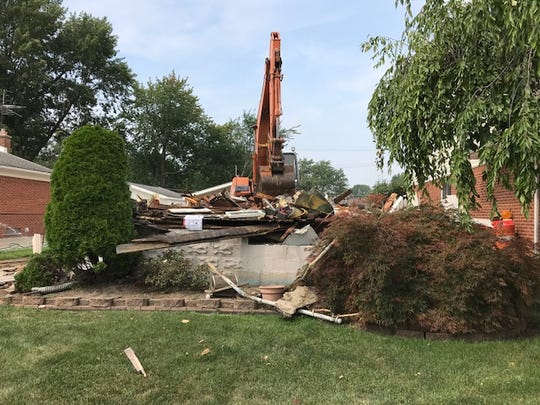 Erica Hammel's two-story St. Clair Shores home lies in a heap Monday, Aug. 27, 2018. A new house will be built in its place.
