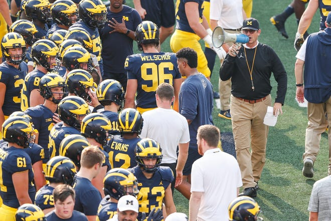 Michigan head coach Jim Harbaugh, right, talks to players during an open practice at Michigan Stadium in Ann Arbor, Sunday, Aug. 26, 2018.