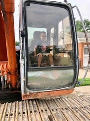 Wyatt Rewoldt, 5, sits in a back hoe before a wrecking crew begins to tear down the St. Clair Shores house he shares with his mother, Erica Hammel.