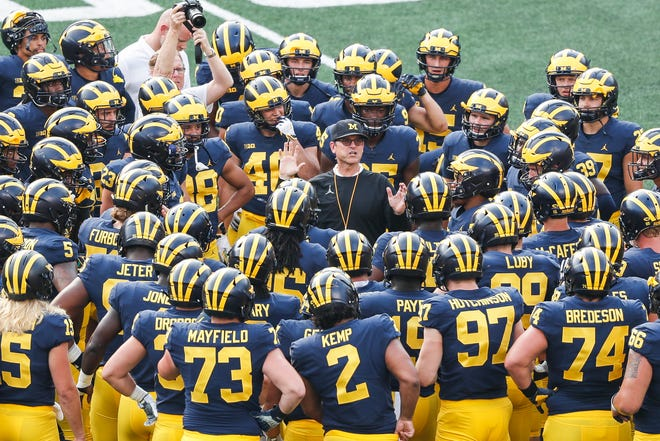 Michigan head coach Jim Harbaugh talks to players during an open practice at Michigan Stadium in Ann Arbor, Sunday, Aug. 26, 2018.