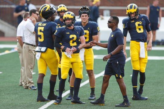 Michigan quarterback Shea Patterson (2), center, talks to assistant head coach Pep Hamilton during an open practice at Michigan Stadium in Ann Arbor, Sunday, Aug. 26, 2018.
