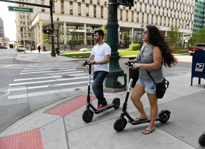 Cristian Rubio, 23, and Cherlene Sousa, 22, both of Detroit wait at the corner on Bird scooters in Detroit last week. This was their first ride on the scooters and they said they were enjoying it. Bird scooters have been in Detroit for about one month.