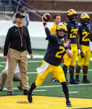 Michigan quarterback Shea Patterson (2) throws a pass while watched by head coach Jim Harbaugh, left, during a preseason open practice session Sunday at Michigan Stadium. Patterson is a transfer from Mississippi and has been named the starter by Harbaugh.