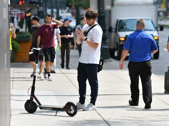 Kellin Wirtz, 24, of Trenton who works downtown, takes a photo of the Bird scooter and then uses the app to lock it after he arrives at his destination in Detroit on Aug. 27, 2018.